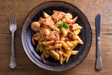Shrimp pasta with sun dried tomatoes and basil in creamy mozzarella sauce. View from above, top...