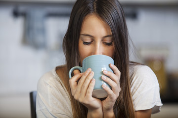 Woman drinking coffee in the morning at kitchen