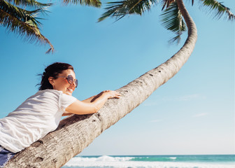 Carefree time summer vacation. Smiling woman lies on the palm tree