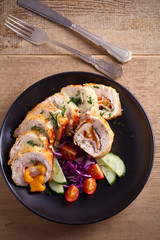 Chicken wrapped with ham and cheddar cheese; vegetables in black plate on wooden table. vertical