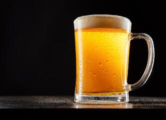 Mug of beer against black background