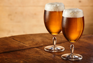Two stemmed glasses of fresh draft or craft beer