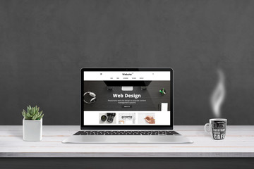 Wall Mural - Web design agency presentation with responsive, flat web site design on laptop display. Cup of coffee and plat beside. Black wall in background.