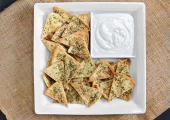 Top view of homemade spicy pita chips and dip.