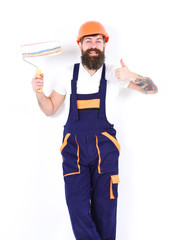 Renovation and decoration concept. Cheerful painter, decorator shows thumb up gesture, while holds paint roller, white background. Man with beard and mustache in helmet and overalls with paint roller.