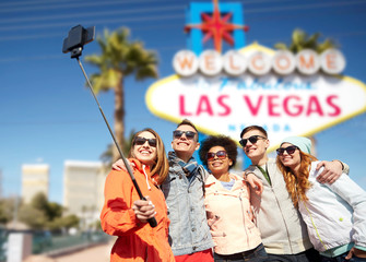 summer holidays, vacation, tourism and travel concept - group of smiling teenage friends taking picture by smartphone selfie stick over welcome to fabulous las vegas sign background