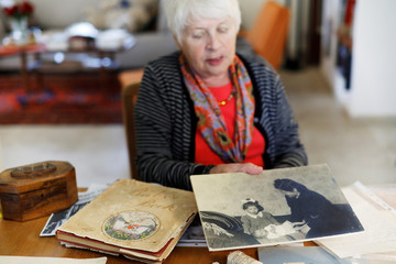 Holocaust survivor Betty Kazin Rosenbaum, 76, holds an old photograph of herself as a child with her mother and baby brother, as she sits in her house in Zichron Yaakov, Israel