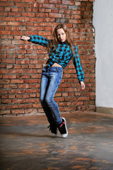 Girl teenager pose movement dance in loft indoors,brown brick wall background.Young stylish hipster woman 9-13 years in bright blue plaid shirt,jeans,sneakers.High fashion urban,youth style.