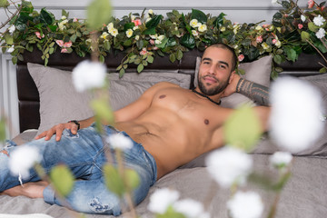 Smiling handsome muslim man with bare chest lying on the gray cozy bed