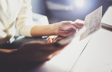 Enjoying business travel concept. Young beautiful brunette tourist girl travelling on the train sitting near the window using smartphone,holding ticket hands.Horizontal closeup.