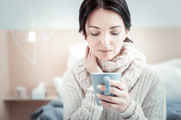 Calm and tea. Thoughtful cute pleasant woman sitting in the bright room holding a cup of tea and overlooking it.