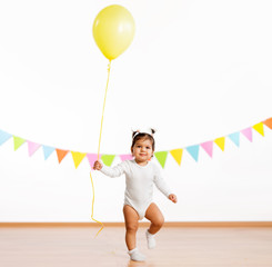 childhood, people and celebration concept - happy baby girl with helium balloons on birthday party