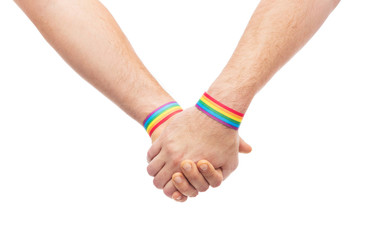lgbt, same-sex relationships and homosexual concept - close up of male couple wearing gay pride rainbow awareness wristbands holding hands