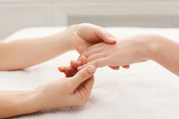 Hand massage at spa salon on white towel