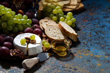 snacks, fruit and Camembert cheese on a dark background