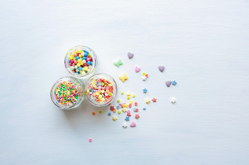 Multicolored sugar elements to decorate sweets on a white background. Top view