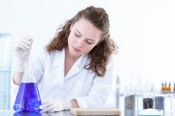 Chemist woman mixing blue solution