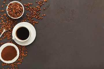 Cup of black coffee and scattered beans on gray background