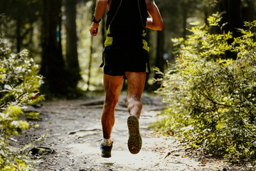 legs runner athlete in spray dirt forest trail run