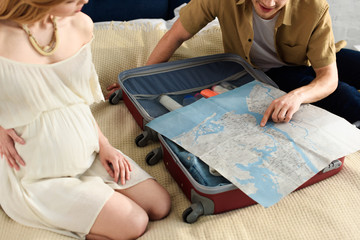 cropped view of pregnant woman and husband preparing for vacation and looking at map