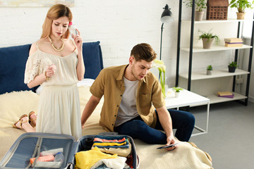 young couple packing suitcase for vacation in bedroom