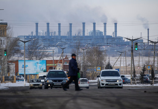 A man walks across a street with Eurasian Resources Group's (ERG) Aksu Ferroalloys Plant seen in the background in the town of Aksu, north-eastern Kazakhstan