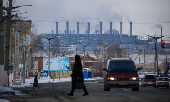 Pedestrians walk across a street with Eurasian Resources Group's (ERG) Aksu Ferroalloys Plant seen in the background in the town of Aksu, north-eastern Kazakhstan