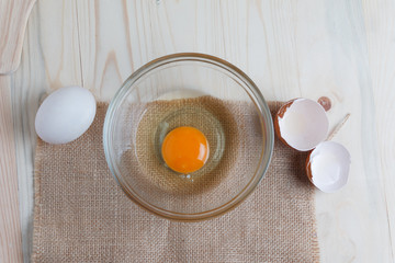 Egg on clear glass bowl over wooden cut board with bakery ingredients select focus shallow depth of field