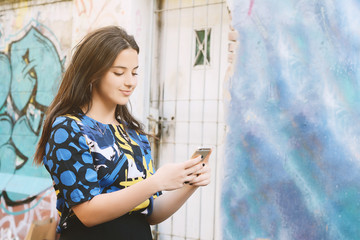Young beautiful woman sending messages with her smartphone