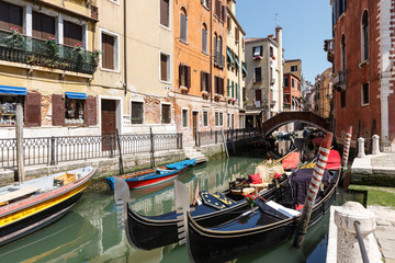 Typical view of gondolas and boats on the canal of Venice. Sunny summer day