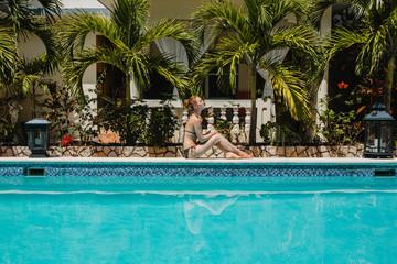 Eine junge Frau erholt sich am Pool
