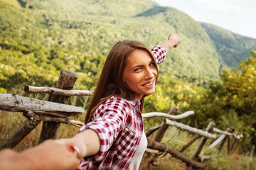 Happy young woman holds the hand of a man in nature