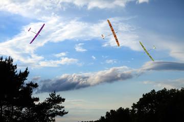 Trzy szybowce zdalnie sterowanie na tle pochmurnego nieba.