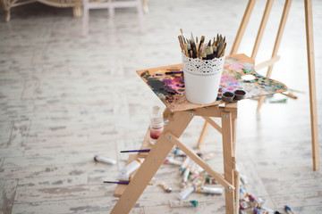 Artistic equipment: easel, paint brushes, tubes of paint, palette and paintings on work table in a artist studio.