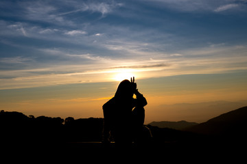 silhouette person feel with background sunrise at top moutain