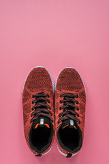Sneakers on a pink background top view copy space