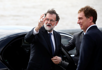 Spain's Prime Minister Mariano Rajoy waves next to Buenos Aires' city vice mayor Diego Santilli during his visit to the Memorial Park in Buenos Aires