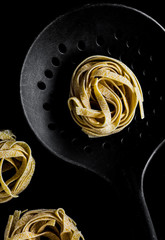 Tagliatelle pasta on black background