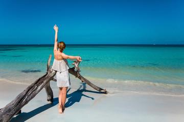 Eine junge Frau spaziert am Strand in der Karibik auf Jamaika
