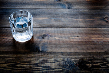 Glass of pure water on dark wooden background top view copy space