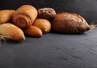 white, gray and rye bread, baguette, roll with sesame seeds on a black background