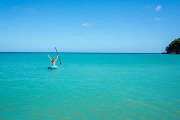 Eine junge Frau paddelt in einem Kajak auf dem Meer in der Karibik auf Jamaika