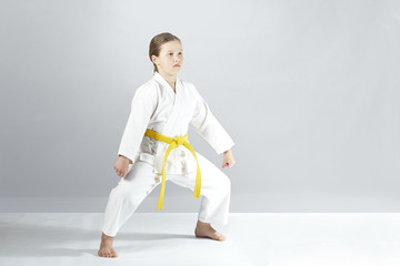 With a yellow belt an athlete stands in a karate rack