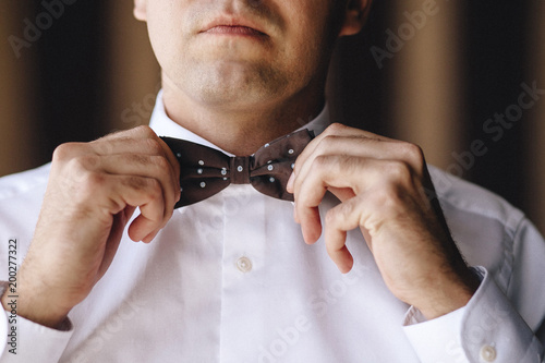 834201f28baa The groom man in a white shirt straightens his hands with a brown bow tie