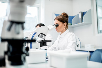 Young female medic in uniform working with microscope making analysis at the laboratory office