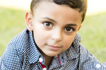 Cute little boy outdoors. Portrait of a little boy in garden, blurred green grass background.