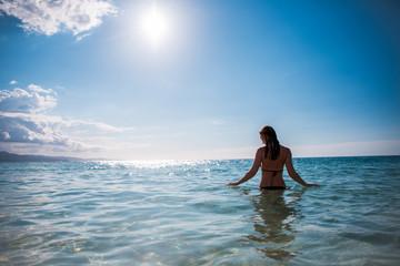 Eine junge Frau schwimmt  in der Karibik auf der Jamaika