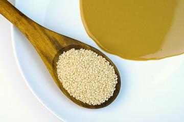 Tahini ( Sesame paste ) and sesame seeds in wooden spoon.