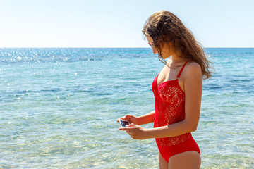 girl hold on smart phone gadget in the beach. Traveler female using mobile on background beach seascape horizon