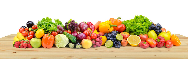 Vegetables and fruits on wooden table boards isolated on white